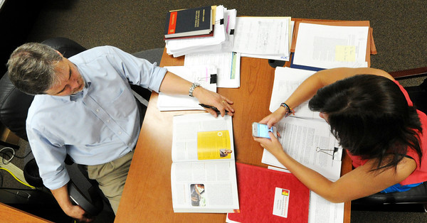 Globe Photo Illusration/T. Rob Brown<br /> Sydney Harris, right, 16, of Carl Junction, daughter of Dr. Eric G. Harris, left, chair of Management & Marketing for PSU's Gladys A. Kelce School of Business, sends her dad and other contacts texts while she sits in her dad's office.