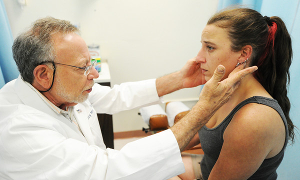 Globe/T. Rob Brown Patient Stormy Coonce, of Joplin, gets examined by Dr. Roy Meek, chiropractic doctor, during a visit to the Community Clinic Thursday afternoon, June 28, 2012.