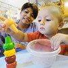 Globe/T. Rob Brown Remington Harpole, 2, stacks up animal-themed crayons as Edna Reyes, of Joplin, lead teacher, looks on Tuesday afternoon, June 19, 2012, at the Learning Junction Educational Center in Joplin.