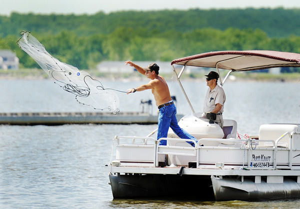 Globe/T. Rob Brown<br /> Kevin Booth casts a net while fishing for bait fish with his father, Homer Booth, both of Goodman, Mo., at Grand Lake, Okla., Tuesday afternoon, June 5, 2012. The duo said they were going to use the bait fish to try to snag some channel catfish.