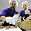 Globe/T. Rob Brown Bob Schatz, left, of Detroit, and coworker Jennifer Jordon, of Denver, try to grab caramel chocolates off the conveyor belt before they fall, while popping a few in their mouths Wednesday morning, June 20, 2012, at the Candy House's factory in downtown Joplin. The two toured several Joplin locations Wednesday and are expected to continue their tour Thursday.