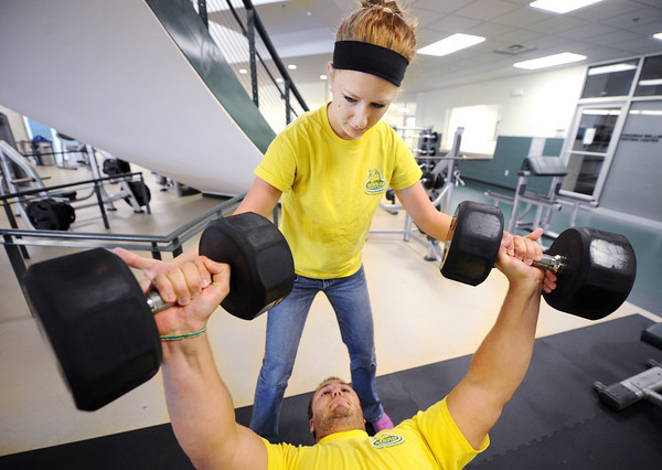 """Globe/T. Rob Brown<br /> Samantha """"Sam"""" Evans, above, of Joplin, spots weight lifter Cody Furr, of Joplin, both senior criminal justice majors, Thursday afternoon, June 7, 2012, at Missouri Southern State University. Evans works at the on-campus job to help defer some of her education costs."""