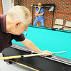 Globe/T. Rob Brown Glenn York, of Webb City, shoots during a game of pool as fellow players Jim Peck, left background, of Joplin, and Bud Johnson, of Baxter Springs, Kan., wait their turn Monday afternoon, June 25, 2012, at the Joplin Senior Center, 22nd Street and Jackson Avenue. The center is extending afternoon hours as a cooling location to give seniors an air-conditioned location during peak heat hours.