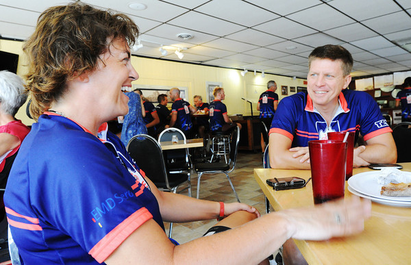 "Globe/T. Rob Brown Jennifer Cherry, left, of Normal, Ill., whose mother died of M.S. after having it for 14 years, shares a laugh with fellow cyclist Brian Sink, of Washington, D.C., and others as they eat lunch and relax Tuesday afternoon, June 26, 2012, at Wheat State Pizza in Pittsburg, Kan. Cherry said she is bycycling across country for M.S. in memory of her mother and Sink said he had wanted to ride across country for years, he found this group and, ""it spoke to me."""