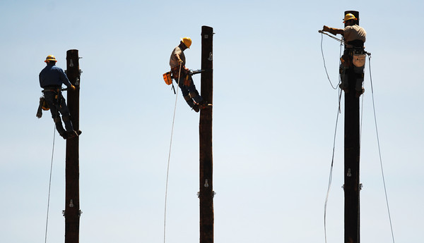 Globe/T. Rob Brown Apprentice linemen, from left, Trevor Gum, Caleb Van Dorn, and Newly Barnett work on utility poles for Empire District Electric Company recently, at the 59 substation near St. Mary's Catholic Church. The poles are part of a temporary fix, according to employees on site, as part of the rebuild to accommodate a new 161,000-volt line.