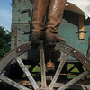 Globe/Roger Nomer<br /> Patrick Goodnight, Oronogo, steps on a wagon wheel to help cover a wagon as he prepares to ride to Ft. Scott on Thursday.