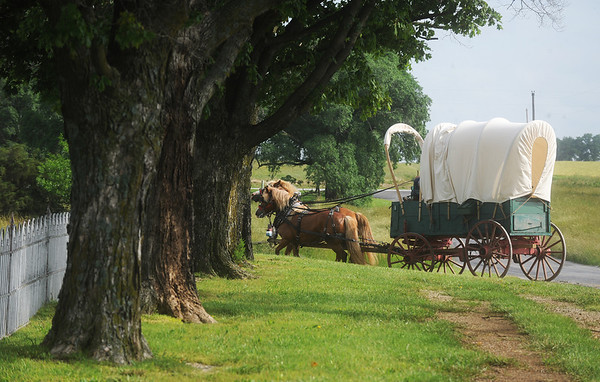 """Globe/Roger Nomer<br /> A covered wagon turns into a cemetary as riders take a stop along the """"Echoes of the Trail"""" ride on Thursday."""