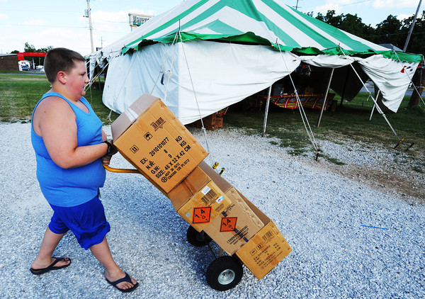 Globe/T. Rob Brown<br /> Kyle Richardson, 13, of Webb City, helps unload a truck for the Jake's Fireworks stand his family operates near the intersection of 7th Street and Duquesne Road Saturday afternoon, June 29, 2013.