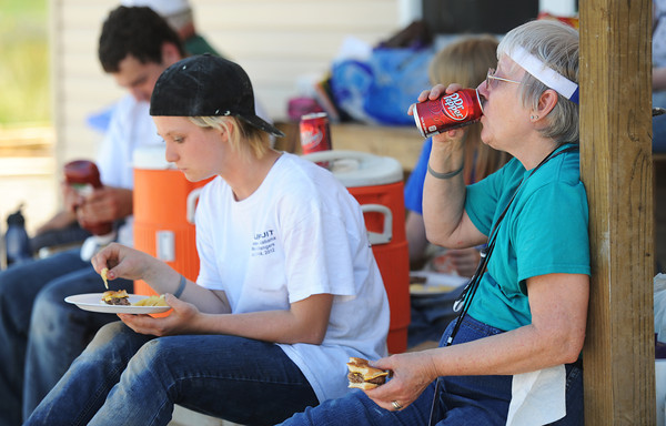 """Globe/T. Rob Brown<br /> Barbara Boviall (right) of Karnak, Ill., and Heather Clark, 17, of Palmyra, Ill., members of the """"Sore Thumbs"""" work group, take a lunch break Friday afternoon, June 28, 2013, in a Rebuild Joplin home being constructed in the 1300 block of East 24th Street."""