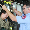 Globe/Roger Nomer<br /> Ryan McCann helps Lage Grigsby, 16, try on his firefighter helmet during Friday's reunion at the Quapaw Tribe station.