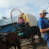 """Globe/Roger Nomer<br /> Larry Osborn, Asbury, ties down his wagon as Jim Bohannon, Neosho, rides out on the """"Echoes of the Trail"""" ride on Friday from Liberal."""
