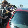 Globe/Roger Nomer<br /> (from left) Nathan Wagner, Carl Junction, Luke Nelson, Joplin, Alexia Tignor, Carl Junction, and David Walker, Carl Junction, wash a car to raise money for a trip to a Skills USA competition this summer.  On Saturday, these high school seniors were raising money to compete further in the Skills USA contest after placing first in state in the entrepreneurship category.  They washed cars at Firestone on Rangeline Road.