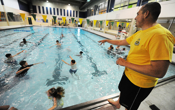 """Globe/T. Rob Brown<br /> Stephan Jakovljevic (right), MSSU lifeguard and swimming instructor, leads a class during the """"World's Largest Swimming Lesson"""" event Tuesday morning, June 18, 2013, at MSSU's Aquatic and Racquetball Center beneath Young Gymnasium."""