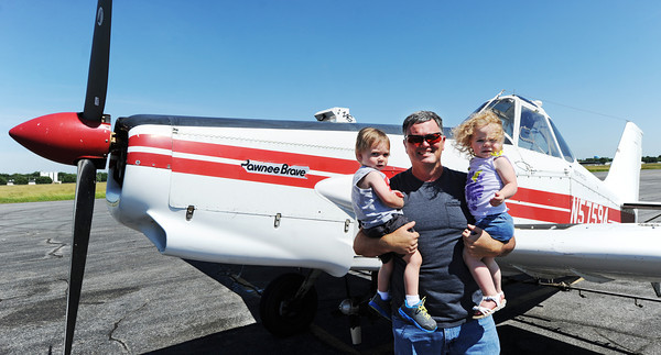 Globe/T. Rob Brown<br /> Tim Kellogg of Riverton, Kan., holds his 1-year-old grandchildren Hayden Kellogg of Columbus, Kan., and Andee Chesnut of Baxter Springs, Kan., in front of his Piper Brave crop dusting airplane at the Miami Regional Airport.