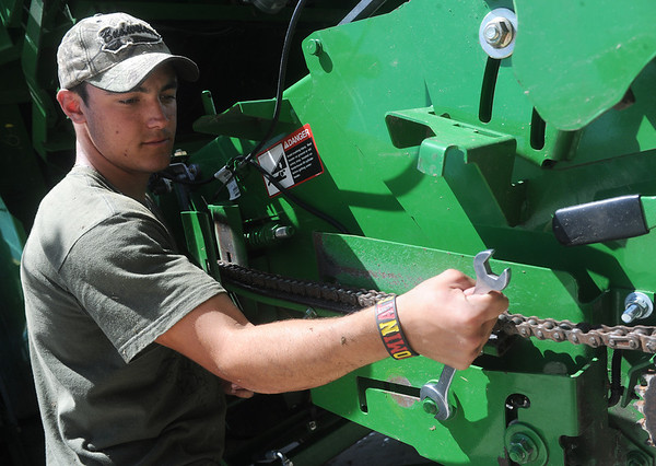 Globe/Roger Nomer<br /> Josh Jarnagin works on a combine at Kyle Kirby's farm near Liberal on Monday afternoon.