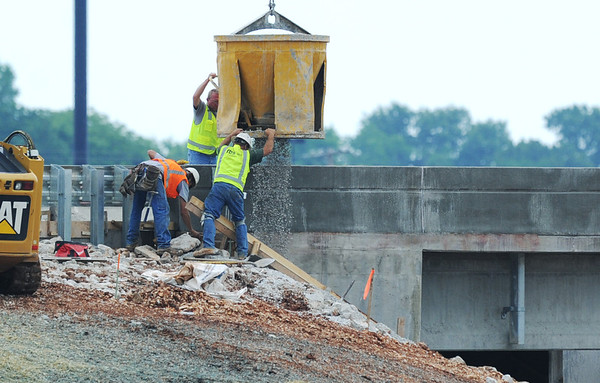 Globe/Roger Nomer<br /> Workers spread gravel along an embankment at the I-44 interchange on Rangeline Road on Tuesday afternoon.