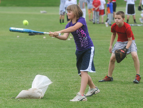 Globe/Roger Nomer<br /> Amber Ross, 10, Chetopa, hits a pitch while Tyler Warde, 11, Webb City, plays catcher during the Joplin Outlaws Youth Clinic at Joe Becker Stadium on Tuesday morning.