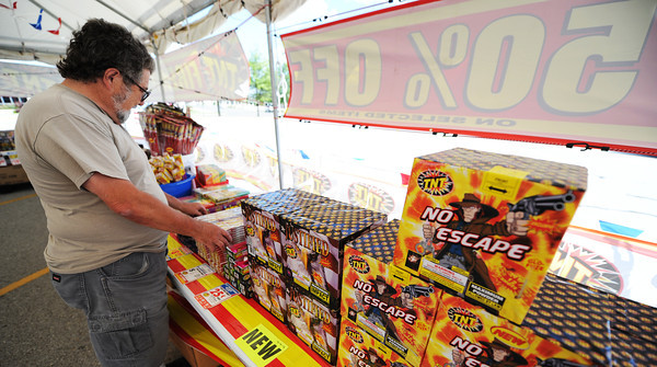 Globe/T. Rob Brown<br /> Melvin Stapp, salesman for the Monark Baptist Church youth group's TNT Fireworks tent in the Walmart Supercenter parking lot in Neosho, arranges the tent's display Saturday afternoon, June 29, 2013.