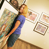 Globe/Roger Nomer<br /> Debbie Reed hangs a picture she painted in the Mosiacs art gallery on East 20th Street on Monday afternoon.  The city of Joplin plans to make improvements to 20th Street with grant money.