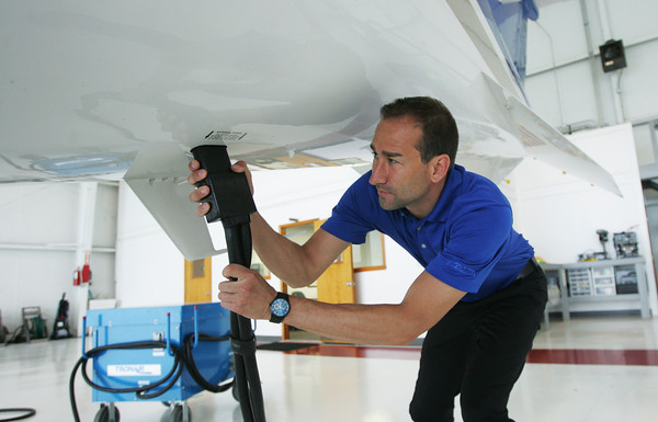 Globe/Roger Nomer<br /> Pilot Mitch Ochs hooks up an auxiliary power cable to a plane used for Tamko flights at the Joplin Regional Airport on Monday, June 17, 2013.