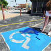 Globe/T. Rob Brown<br /> Tammy Willhoit of Neosho, a volunteer from Arvest Bank, helps paint handicap accessible parking spaces during the United Way Day of Action Friday morning, June 21, 2013, at the Community Clinic.