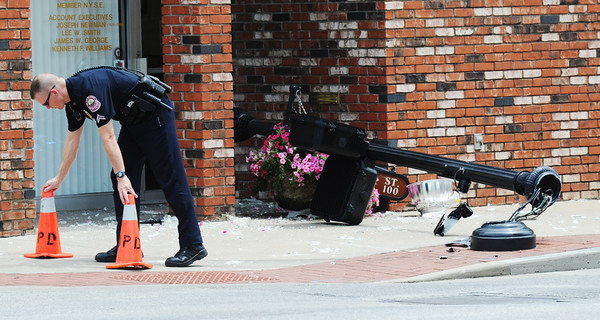 Globe/T. Rob Brown<br /> A Joplin police officers sets out safety cones to warn pedestrians of broken glass on the pavement as a result of a downtown decorative light pole being knocked down by a vehicle Tuesday afternoon, June 25, 2013, on Main Street near the intersection with Fourth Street.