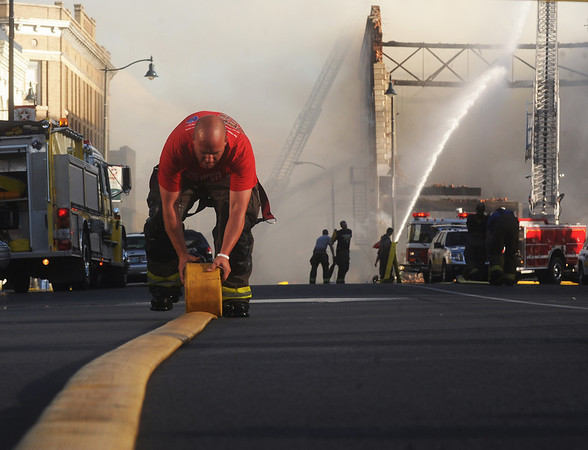 Globe/Roger Nomer<br /> Carthage Firefighter Josh Estes rolls up a hose at the scene of a fire on the Carthage square on Saturday evening.