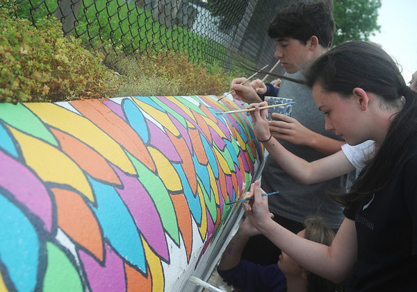 Globe/Roger Nomer<br /> Nathan Sell, 17, and Tristen Palmer, 16, paint a mural on the grounds of Irving Elementary on Tuesday morning.  Sell and Palmer are part of a youth choir from Asbury United Methodist Church, from Madison, Ala., on tour through the country.  The choir stopped in Joplin to volunteer with Art Feeds and other local organizations for rebuilding efforts.