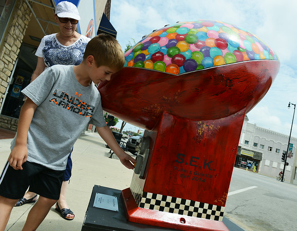 Globe/Roger Nomer<br /> Jackie Betz, Pittsburg, and her grand nephew Thaddeus Mayo, 7, Houston, Texas, check out a gumball-themed football created by Steve and Cindy Head in downtown Pittsburg on Friday.