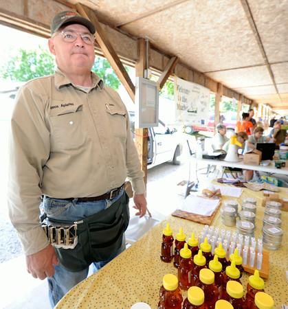 Jann Amos looks into the crowd of people on Friday at the Webb City Farmer's Market. Amos said he has seen an increase of ticks this year.<br /> Globe | laurie Sisk