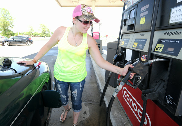 Kristin Hope, Joplin, prepares to pump gas at Horton's Pizza Plus in Pittsburg on Thursday. Hope said she believes gas prices are still too high.<br /> Globe | Laurie Sisk