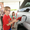 Brayden Dick, 8 pumps gas as his mom, Lindsey Barnes and sister Olivia wade wait at Casey's on Second and Maiden Lane on Friday. Barnes said she is looking forward to the day when gas prices finally go down.<br /> Globe | Laurie Sisk