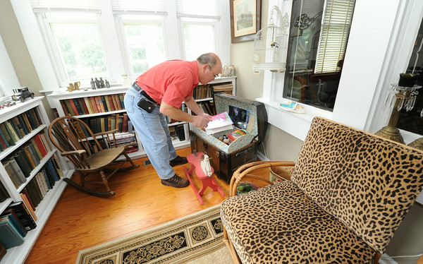 Mark Callihan organizes a toy chest on a porch that he and his wife, Paula Callihan transformed into a children's playroom and library at their historic house on 108 South Moffett in Murphysburg. The couple bought the house from family after it had been vacant for 18 years.<br /> Globe | Laurie Sisk