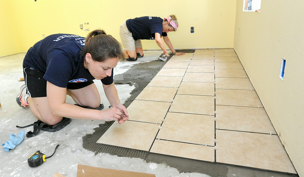 Farmers Insurance volunteers emily Bruschi, Kansas City and Susan Brooks, Overland Park, kan., install new flooring at a house at 1004 Central on Tuesday morning. The two are part of a group of about 35 volunteers from Farmers who are working with Rebuild Joplin.<br /> Globe | Laurie Sisk