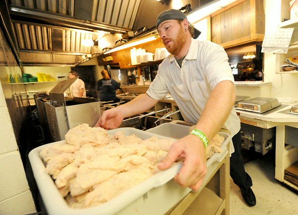 Kris Miitchell prepares to fry another batch of chicken on a busy Saturday night at Chicken Annie's north of Frontenac. The restaurant is preparing to celebrate its 80th anniversary.<br /> Globe   Laurie Sisk