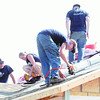 Farmers Insurance volunteers from the Kansas City area help install roofing on a house at 2423 Picher on Tuesday morning.<br /> Globe | Laurie Sisk
