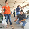 Steve McKarus, of the Jasper County Health Department and Karen Lee demonstrate the importance of spraying near the bottom of the pant leg to ward off ticks. Because of an increase of ticks this year, McKarus was at the Webb City Farmers Market on Friday distributing information about insects.<br /> Globe | Laurie Sisk