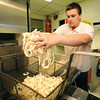 Josh West prepares to deep fry a batch of hand-breaded onion rings Saturday night at Chicken Annie's north of Frontenac. The restaurant is preparing to celebrate its 80th anniversary.<br /> Globe | Laurie Sisk