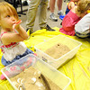 Three-year-old Evelyn Miller finds a plastic sea shell inside a tub of sand during Explore and Play Beach Day on Saturday at the Joplin Public Library.<br /> Globe | Laurie Sisk