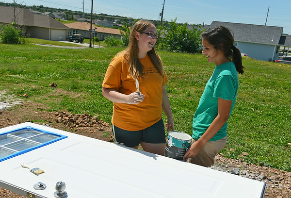 Globe/Roger Nomer<br /> Makella Coulson, 15, Grain Valley, talks with Jessica Johnson, Springfield, about the door of a house on Picher on Tuesday morning. Johnson is an Americorp volunteer with Rebuild Joplin who also ran the Joplin Memorial Half Marathon last month.