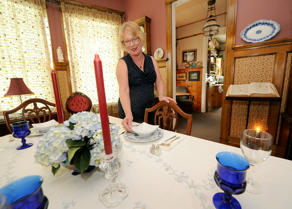 Paula Callihan sets the dining room table in her and her husband Mark's historic house on 108 South Moffett in Murphysburg. The couple bought the house from family after it had been vacant for 18 years.<br /> Globe   Laurie Sisk