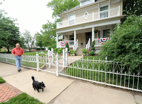 Murphysburg resident Mark Callihan walks a neighbor's dog, Skipper, past a house on 218 South Sergeant in historic Murphysburg. Callihan is a longtime resident of the neighborhood.<br /> Globe | Laurie Sisk