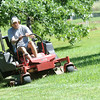 Steve Metsker, of The Lawn Guy mows a large yard in the Wildwood development area on Friday. The business has noticed a significant increase in work with the increase of rain.<br /> Globe | Laurie Sisk