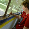 Globe/Roger Nomer<br /> Penny Collins, a fuel accountant for Empire Electric, paints the dining hall at the Childress Scout Camp on Friday.