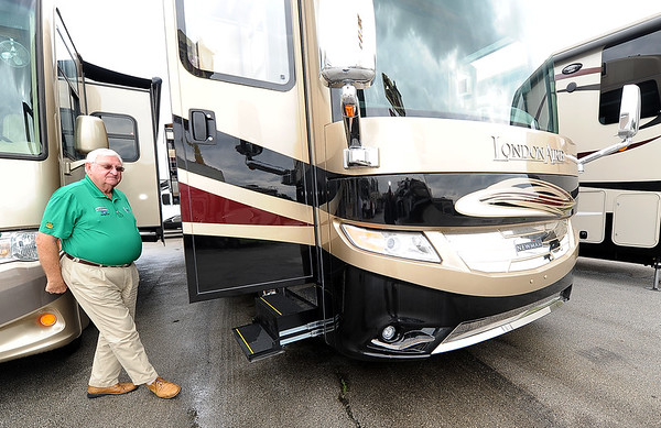 Marty Lown, of Coachlight RV, stands outside the Newmar Londonaire motorhome on Thursday.<br /> Globe | Laurie Sisk