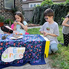 From the left: Anie Spiering, 6, Levi Spiering, 8 and Elie Spiering, 9, set up their own nature center in the front yard of their North Byers street home. The trio supplied rocks, plants and other nature related items for visitors to look at through a magnifying glass and sold homemade bird feeders in hopes of raising money to buy a pet fish.<br /> Globe | Laurie Sisk