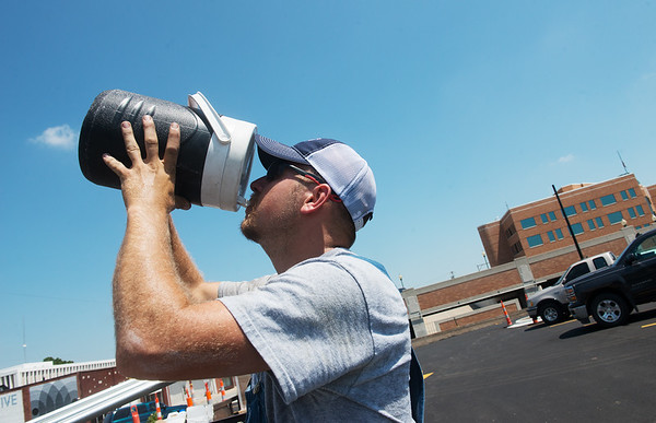 Globe/Roger Nomer<br /> Craig Roberts, with Joplin Industrial Electric, takes a drink of water while working on the Empire parking lot on Seventh Street on Tuesday.
