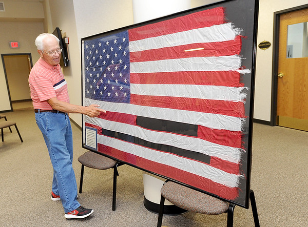 Allen Shirley, president of the Friends of the Museum board, points out areas of the Joplin Tornado Flag, which were sewn into the 911 Flag.<br /> Globe | Laurie Sisk