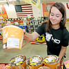 Black Market Fireworks employee Alyssa Lightfoot, 16, restocks shelves in preparation for a busy week on Wednesday afternoon at Black Market on North Main Street.<br /> Globe | Laurie Sisk