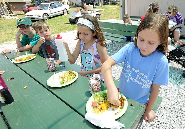 From the left: Silas Luzadder, 8, Zeke Luzadder, 6, Sophia Crane, 10 and Savannah Crane, 8, enjoy a kids free lunch on Thursday at the Webb City Farmers Market. About 200 kids enjoyed Mexican fare as part of the ongoing program.<br /> Globe | Laurie Sisk